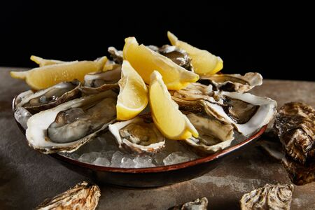 close up of oysters and lemons in bowl with ice isolated on black Stock Photo