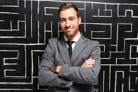 handsome and smiling businessman in suit with crossed arms standing near labyrinth