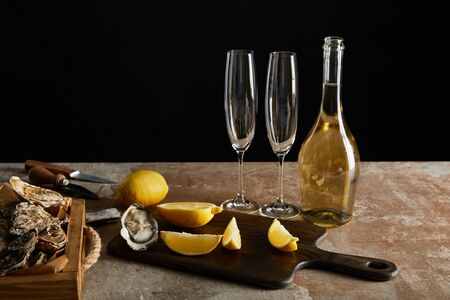 delicious oysters near lemons and bottle with sparkling wine isolated on black