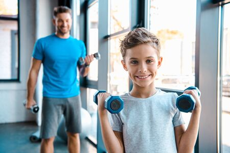 selective focus cute kid exercising with dumbbells near father