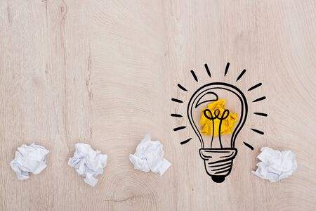 top view of crumpled paper balls and illustration of light bulb on wooden table, business concept