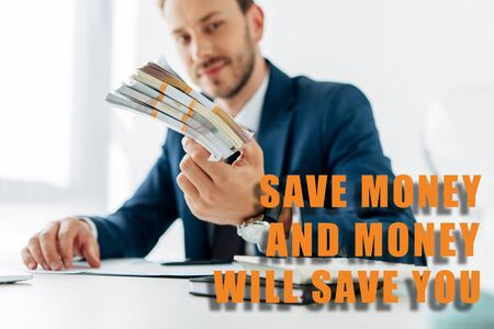 selective focus of businessman holding money in office with save the money and money will save you illustration