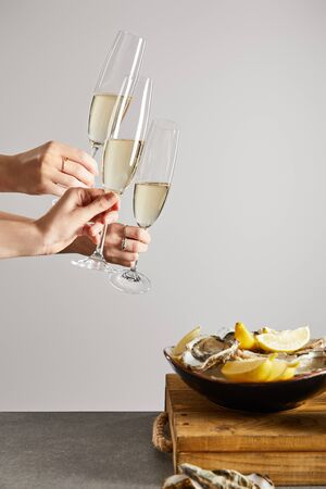 cropped view of women clinking champagne glasses with sparkling wine near bowl with oysters and fresh lemons isolated on grey