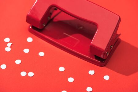 high angle view of holepunch with paper circles on red background