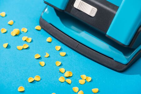 high angle view of holepunch with paper circles on blue background