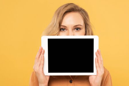 Blonde woman covering face with digital tablet with blank screen isolated on yellow Archivio Fotografico - 134812818