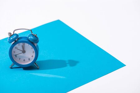 high angle view of alarm clock and blue paper isolated on white 版權商用圖片 - 134812821