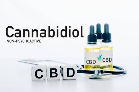 cubes with cbd lettering near oil and stethoscope isolated on white with non-psychoactive cbd illustration