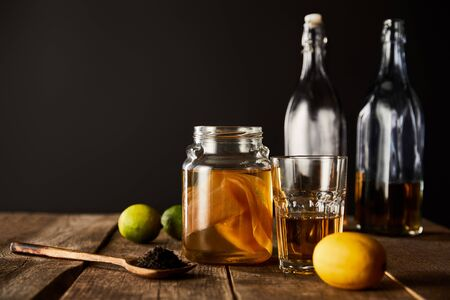 glass jar with kombucha near lime, lemon, spice and bottles on wooden table isolated on black Zdjęcie Seryjne