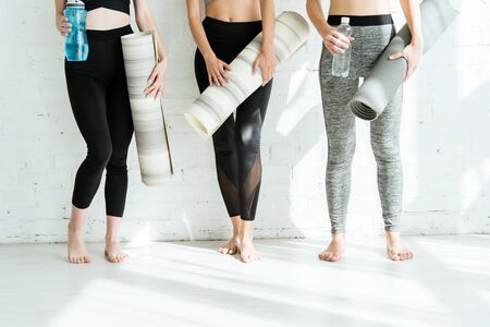 cropped view of three young women holding yoga mats and bottles with water near white wall 스톡 콘텐츠