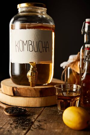 glass jar with kombucha on wooden table isolated on black