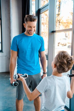 selective focus happy father looking at cute son exercising with dumbbells in gym