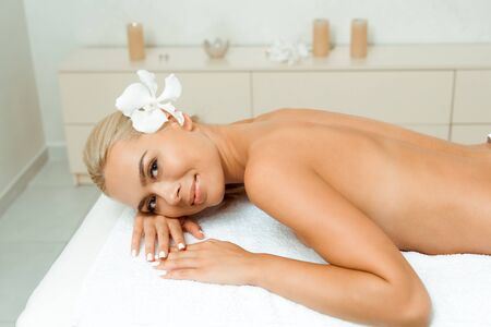 high angle view of attractive and smiling woman with flower looking at camera and lying on massage table in spa