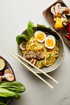 top view of traditional asian ramen in bowl near chopsticks, vegetables on grey surface Stock Photo