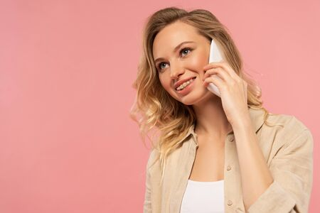 Smiling blonde woman talking on smartphone isolated on pink