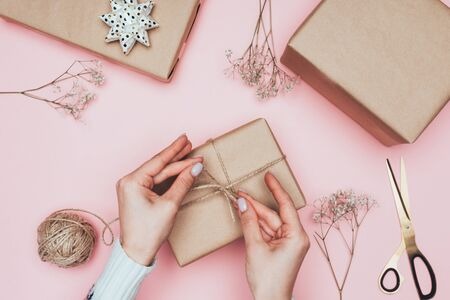cropped view of girl packing christmas presents with craft paper, twine and flowers, isolated on pink 版權商用圖片