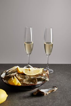 champagne glasses with sparkling wine near delicious oysters and lemons in bowl isolated on grey