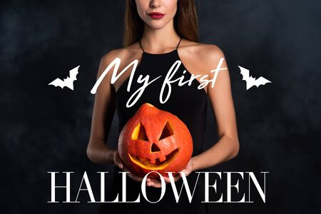 cropped view of woman holding halloween pumpkin with my first Halloween lettering