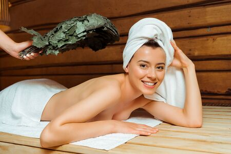 cropped view of woman hitting her friend with birch broom in sauna
