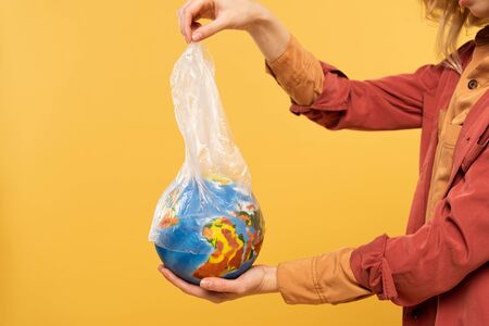 Cropped view of woman holding globe and plastic package isolated on yellow, global warming concept