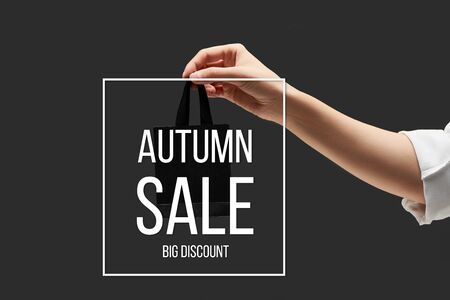 cropped view of woman holding small black shopping bag in hand isolated on black with autumn sale illustration 版權商用圖片