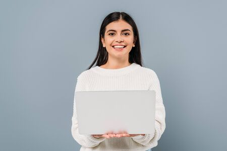 smiling pretty brunette girl in white sweater holding laptop isolated on grey