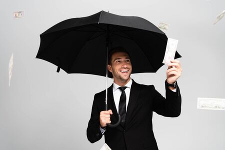 handsome and smiling businessman in suit holding umbrella and holding dollar banknote isolated on grey