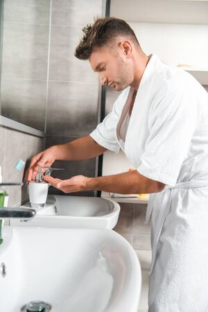selective focus of handsome man in bathtub standing with cupped hand near bathroom sink