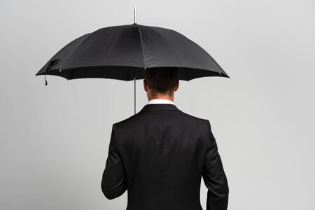 back view of businessman in suit holding umbrella isolated on grey 스톡 콘텐츠
