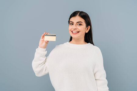 smiling pretty girl in white sweater holding credit card isolated on grey