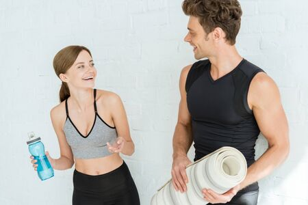 cheerful woman with sports bottle smiling to man holding yoga mat 스톡 콘텐츠