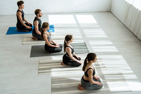 high angle view of five young people meditating in thunderbolt pose