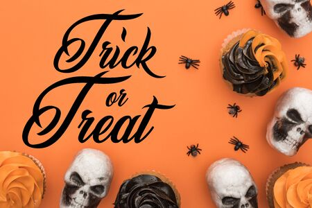 top view of delicious Halloween cupcakes with spiders and skulls on orange background with trick or treat illustration