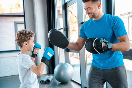 happy father and cute son boxing in gym