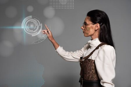 cropped view of steampunk young woman in white blouse pointing with finger at digital illustration on grey Stock fotó