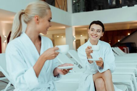 smiling friends in white bathrobes talking and holding cups in spa 스톡 콘텐츠