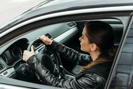 Side view of female taxi driver holding steering wheel 스톡 콘텐츠