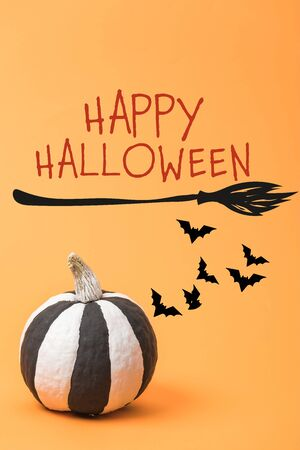 striped painted black and white Halloween pumpkin on orange colorful background with bats, with broom and happy Halloween illustration