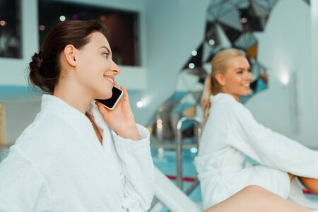selective focus of attractive and smiling woman talking on smartphone and friend on background in spa 스톡 콘텐츠