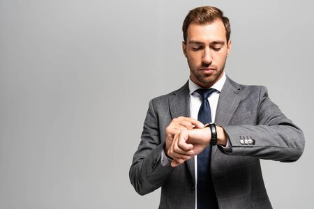handsome businessman in suit looking at wristwatch isolated on grey 스톡 콘텐츠