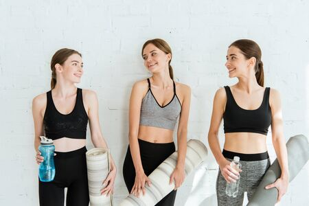 three cheerful women talking while standing near white wall with yoga mats and bottles of water