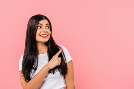 smiling pretty brunette girl pointing with finger at copy space isolated on pink