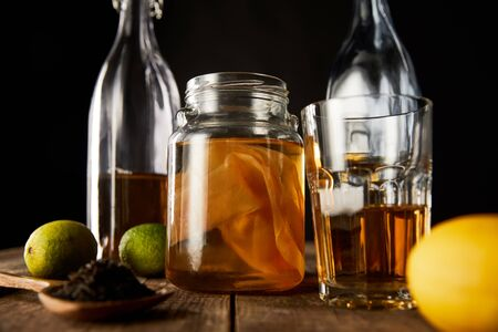selective focus of glass jar with kombucha near lime, lemon, spice and bottles on wooden table isolated on black Zdjęcie Seryjne