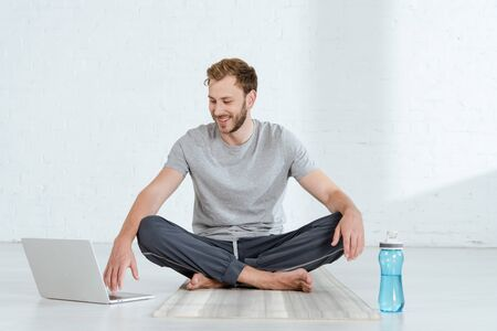 smiling man sitting in easy pose near laptop and sports bottle