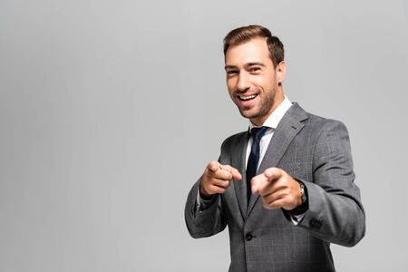 smiling and handsome businessman in suit pointing with fingers isolated on grey