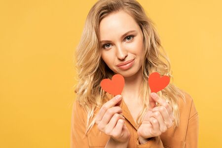 Smiling blonde woman holding paper hearts isolated on yellow