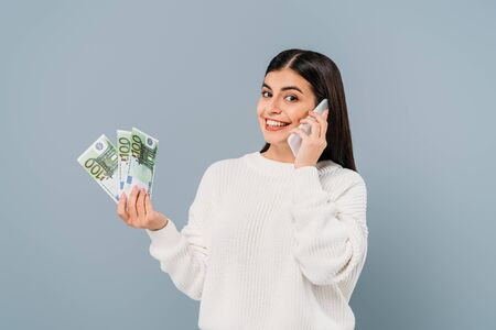 smiling pretty girl in white sweater holding euro banknotes and talking on smartphone isolated on grey