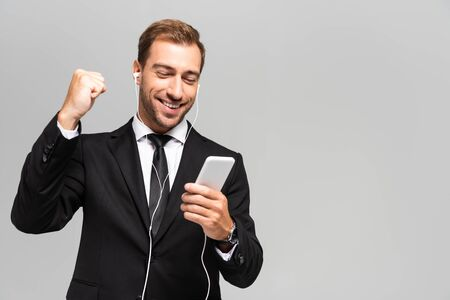 handsome and smiling businessman in suit with earphones using smartphone and showing yes gesture isolated on grey 스톡 콘텐츠