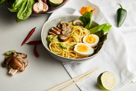 traditional asian ramen in bowl near chopsticks, napkin and vegetables on grey surface Stock Photo