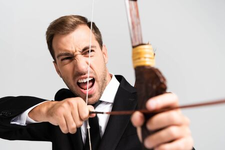 selective focus of angry businessman in suit holding bow and shooting with arrow isolated on grey